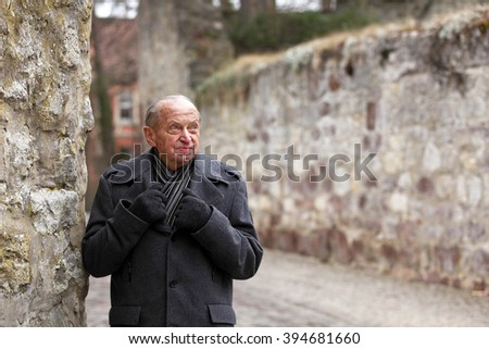 Elderly man standing at the city walls of a historic German town