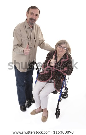 elderly man standing beside a woman sitting on a walker both showing thumbs up - stock photo