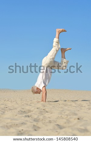 elderly man standing on his hands against the sky - stock photo