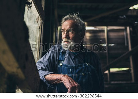 Elderly man staring out of a rustic wooden window in an old rural barn or house with a thoughtful serious expression - stock photo