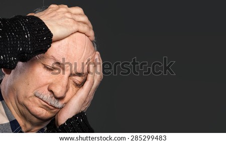 Elderly man suffering from a headache and toothache on gray background with copy-space