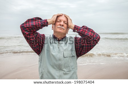 Elderly man suffering from a headache on sea background on foggy day - stock photo