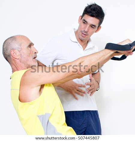 Elderly man suffering in the gym with suspension exercise