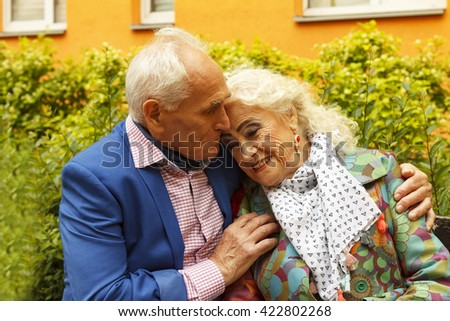 Elderly man tenderly embracing his elderly wife on a bench near a residential building in a modern city. Elderly people wearing fashionable clothes elegant, festive bright make up. - stock photo