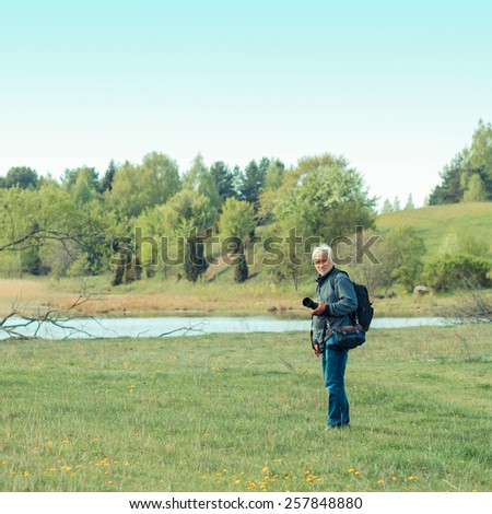 Elderly man travels in wildlife. Portrait of the gray-haired traveler in background of the landscape. Old photographer enjoys traveling and photography - stock photo