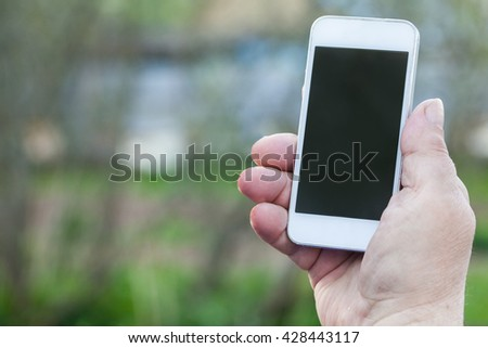 Elderly Man uses his Mobile Phone outdoor, close up
