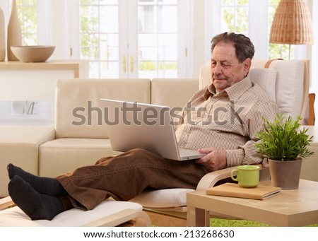 Elderly man using laptop computer at home, sitting in armchair, looking at screen.