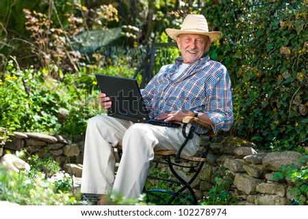 Elderly man using laptop in the park - stock photo