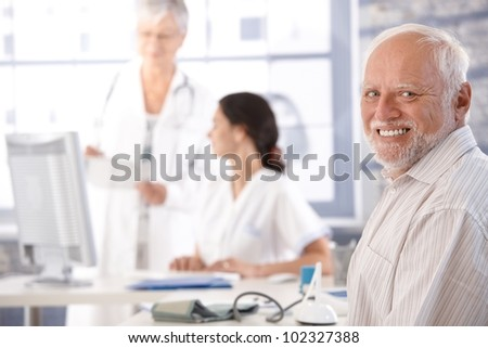 Elderly man waiting for examination at doctor's room, smiling.