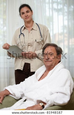 Elderly man waiting for examination, young female doctor at background.? - stock photo