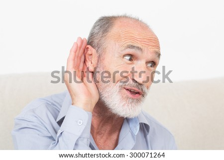 Elderly man with a symbol picture for listening - stock photo