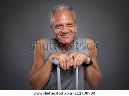 Elderly man with crutches - stock photo