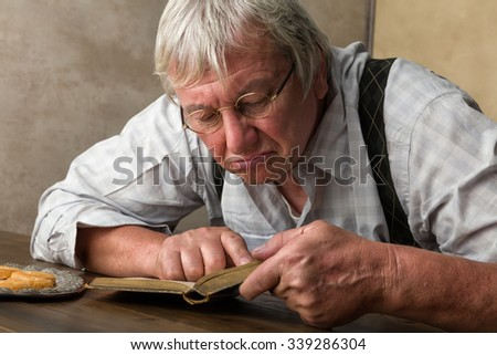 Elderly man with glasses reading a book