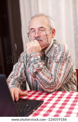 Elderly man with glasses using laptop at home.
