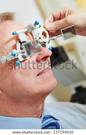 Elderly man with trial frame and trial glasses at optician - stock photo