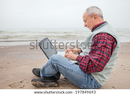 Elderly man working on a computer while sitting on the beach on a foggy day