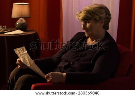 Elderly melancholic woman reading letter from old friend - stock photo