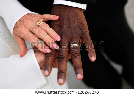 Elderly mixed race newlyweds displaying wedding rings