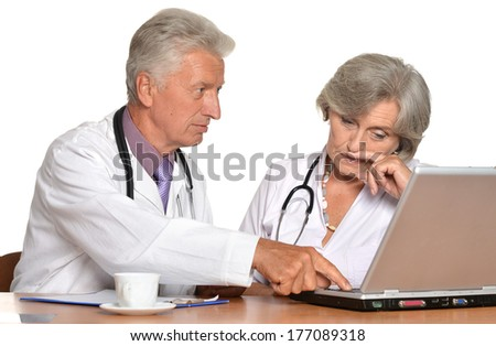 Elderly nice  doctors with a laptop - stock photo
