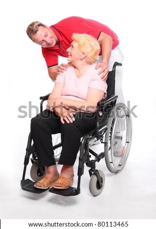 Elderly paraplegic woman sitting in a wheelchair and her male nurse. - stock photo
