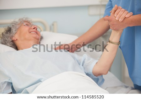 Elderly pateint in hospital bed holding hand of nurse - stock photo