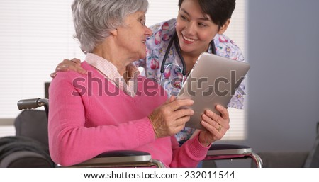 Elderly patient and Asian nurse having fun with tablet - stock photo