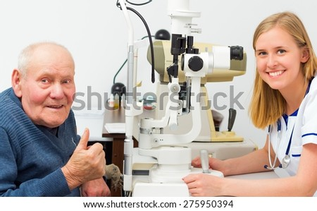 Elderly patient being satisfied with the eye doctor's treatment. - stock photo