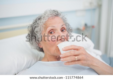 Elderly patient drinking in hospital ward - stock photo