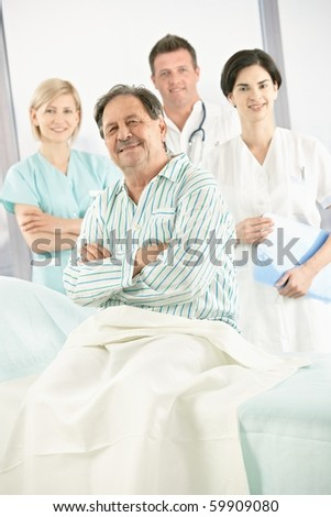Elderly patient in hospital smiling at camera with medical team in background.? - stock photo