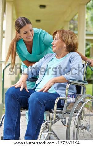 Elderly patient in wheelchair talking to nurse in a hospital garden - stock photo