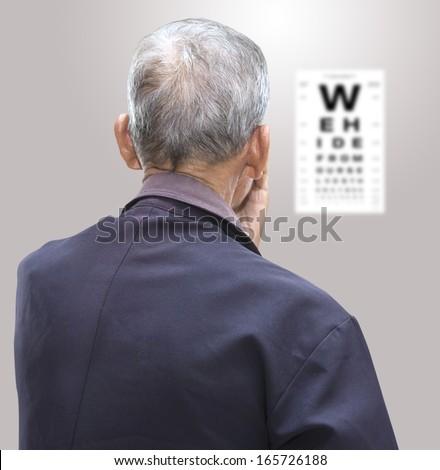 Elderly patient looking at eye chart,Elderly patients seeking eye charts,patient looking at eye chart - stock photo