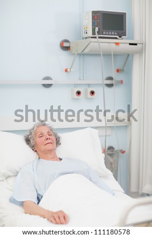 Elderly patient lying with closed eyes in hospital ward - stock photo