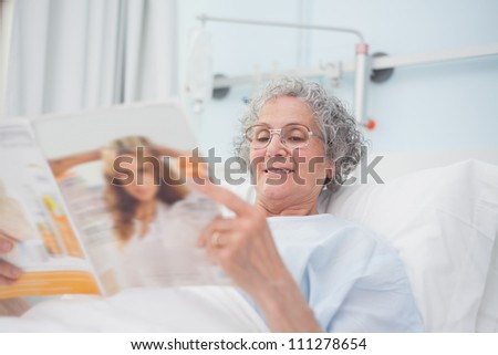 Elderly patient reading a magazine on her bed in hospital ward - stock photo