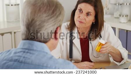Elderly patient talking doctor about prescription in office - stock photo