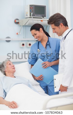 Elderly patient talking to a doctor and a nurse in hospital ward
