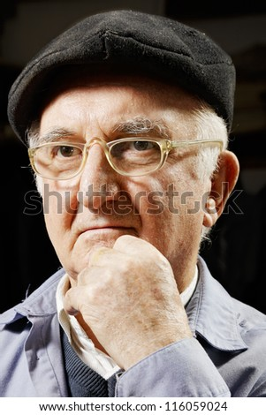 Elderly pensive man in cap and eyeglasses leaning on hand - stock photo