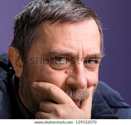 Elderly  pensive man  on a lilac background