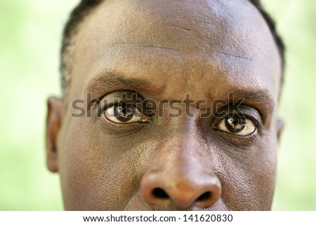 Elderly people and emotions, portrait of serious senior african american man looking at camera against green wall - stock photo