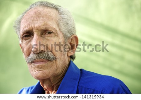 Elderly people and emotions, portrait of serious senior caucasian man looking at camera against green wall - stock photo