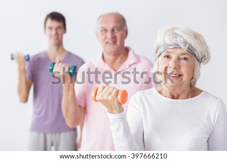 Elderly people and gym instructor during exercises with dumbbells, light background