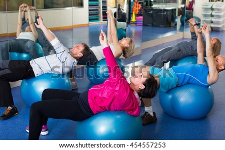 Elderly people stretching in a gym on fitness balls