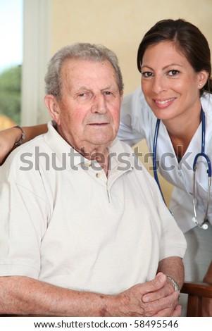 Elderly person with nurse - stock photo