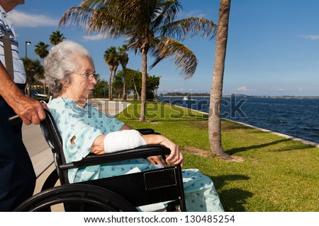 Elderly 80 plus year old woman in a wheel chair convalescing outdoors in a bay setting.