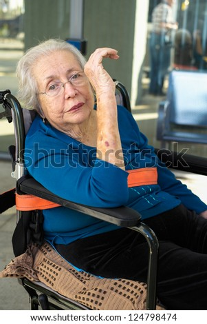 Elderly 80 plus year old woman portrait in a outdoor setting while being transported. - stock photo