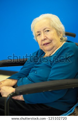 Elderly 80 plus year old woman portrait with a blue background. - stock photo