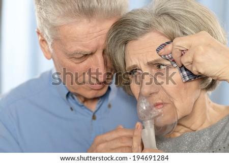 Elderly sad couple making inhalation together closeup - stock photo