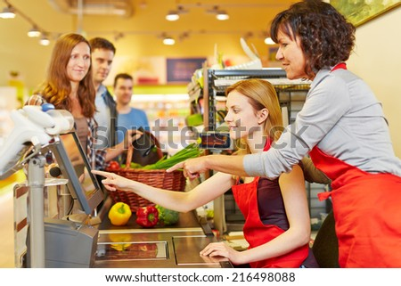 Elderly saleswoman helping young woman at supermarket checkout - stock photo