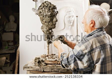 Elderly sculptor making sculpture profile view - stock photo