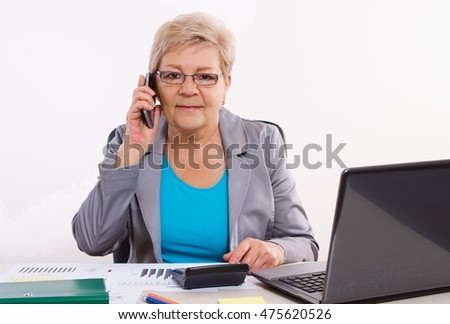 Elderly senior business woman talking on mobile phone and working with calculator and financial charts at her desk in office, analysis of sales plan