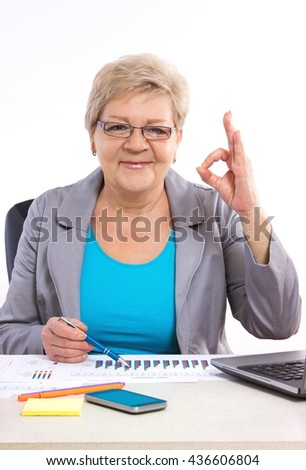 Elderly senior business woman working at her desk in office, analyzing financial charts and showing sign ok, business concept, analysis of sales plan, business report - stock photo